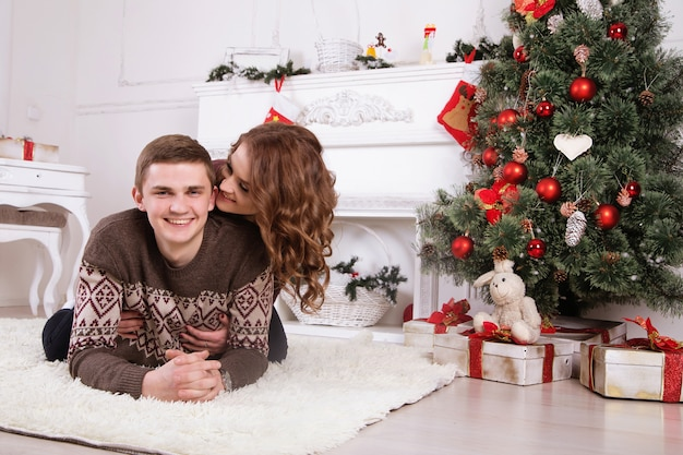Jeune, heureux, couple, embrasser, près, arbre noël, célébrer, nouvel an, ensemble, sourire Photo Premium