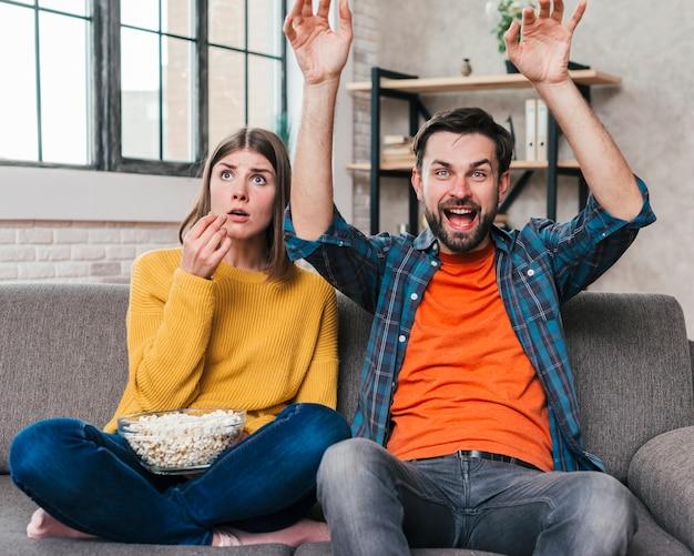 Jeune homme acclamant tout en regardant le match de télévision assis avec sa femme Photo gratuit