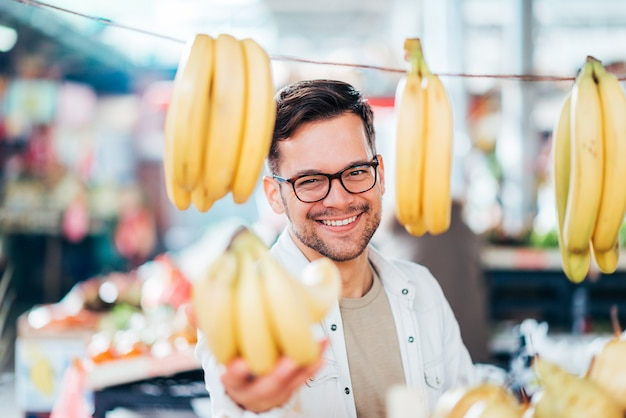 Jeune Homme Achetant Ou Vendant Des Bananes Au Marché Fermier. Photo Premium