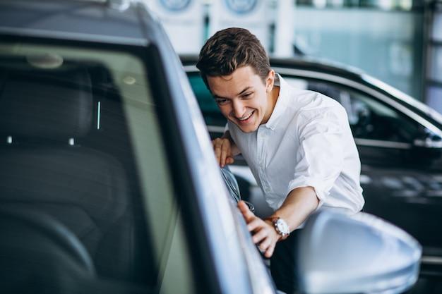 Jeune homme achète une voiture dans une salle d'exposition Photo gratuit