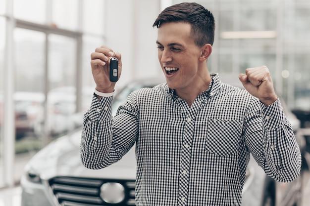 Jeune homme achète une voiture neuve chez le concessionnaire Photo Premium