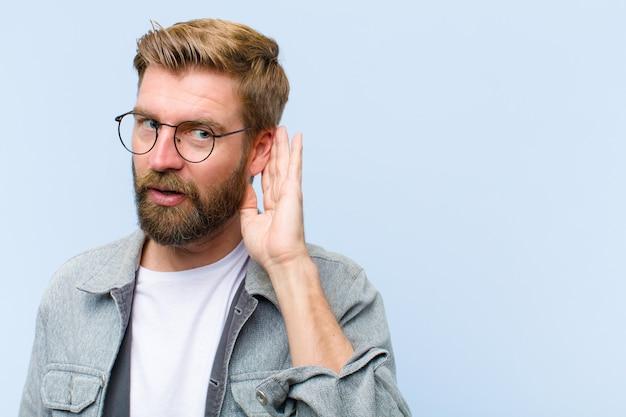 Jeune homme adulte blonde à l'air sérieux et curieux, à l'écoute, essayant d'entendre une conversation secrète ou des commérages, à l'écoute Photo Premium