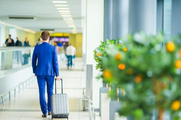 Jeune homme à l'aéroport. casual jeune garçon portant une veste de costume. Photo Premium