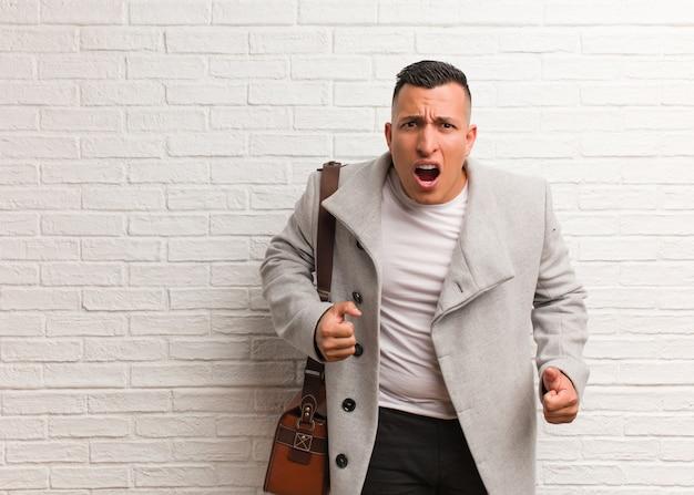 Jeune homme d'affaire latine hurlant très en colère et agressif Photo Premium