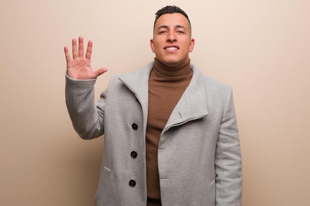 Jeune homme d'affaire latine montrant le numéro cinq Photo Premium