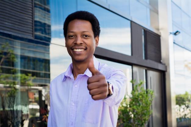 Jeune homme d'affaires abandonnant le pouce. Photo Premium