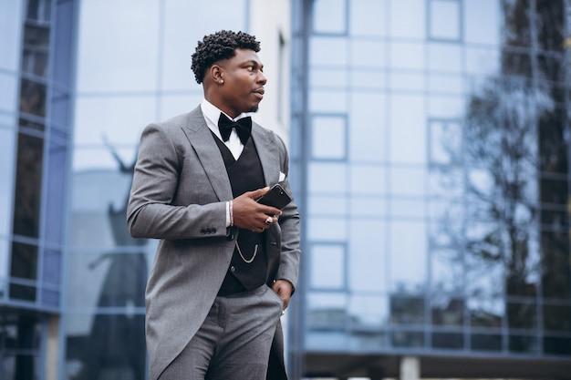 Jeune homme d'affaires africain à l'aide de téléphone Photo gratuit