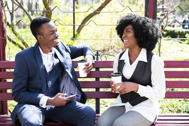 Un jeune homme d'affaires africain et une femme d'affaires assis sur un banc tenant une tasse de café jetable Photo gratuit