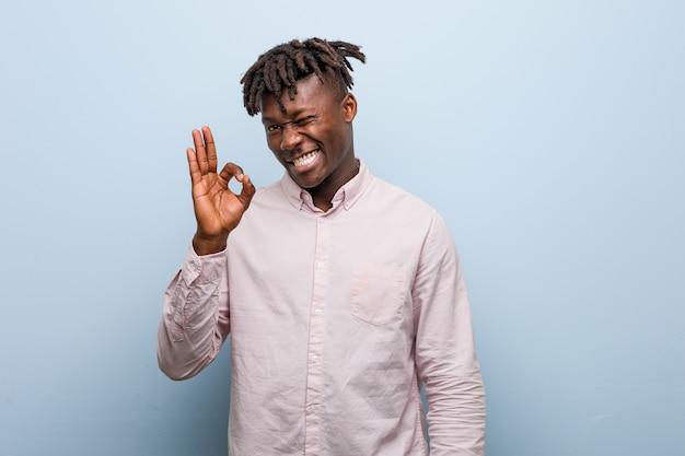 Jeune Homme D'affaires Africain Noir Cligne De L'œil Et Détient Un Geste Correct Avec La Main. Photo Premium