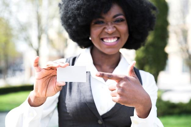 Un jeune homme d'affaires africain, pointant son doigt vers la carte de visite Photo gratuit