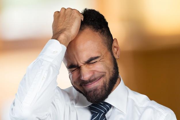 Jeune homme d'affaires afro-américain souffrant de maux de tête après une journée de travail Photo Premium