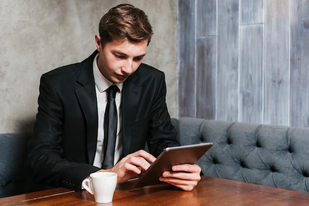 Jeune homme d'affaires à l'aide de tablette Photo gratuit