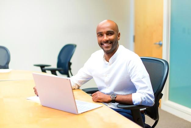 Jeune homme d'affaires américain afro au bureau avec son ordinateur portable Photo Premium