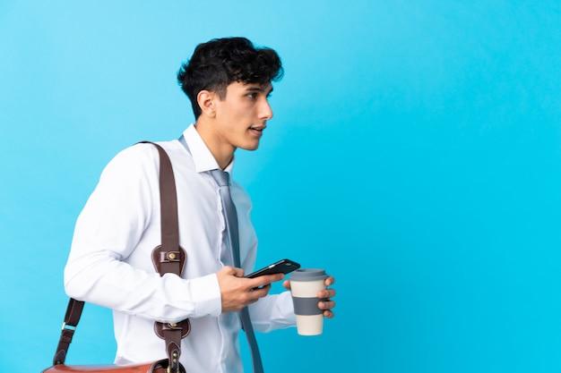Jeune homme d'affaires argentin sur mur bleu isolé Photo Premium