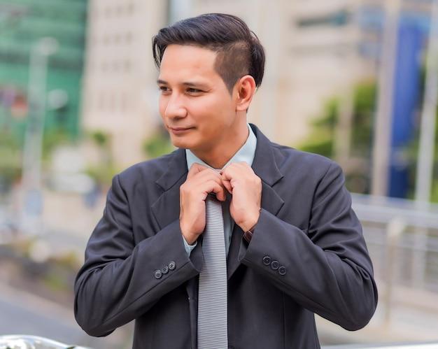 Jeune Homme D'affaires Asiatique Devant Le Bâtiment Moderne Au Centre-ville .concept De Jeunes Gens D'affaires Photo Premium