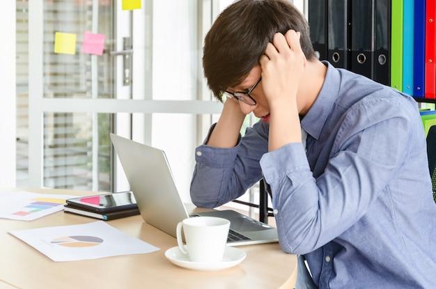 Jeune homme d'affaires asiatique frustré sur son travail et hors de contrôle. stress et maux de tête en cas d'échec du travail au bureau Photo Premium