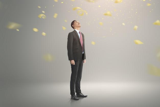 Jeune homme d'affaires asiatique en levant avec des confettis en baisse Photo Premium
