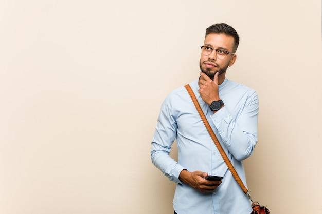 Jeune Homme D'affaires Asiatique De Race Mixte Tenant Un Téléphone à Côté Avec Une Expression Douteuse Et Sceptique. Photo Premium