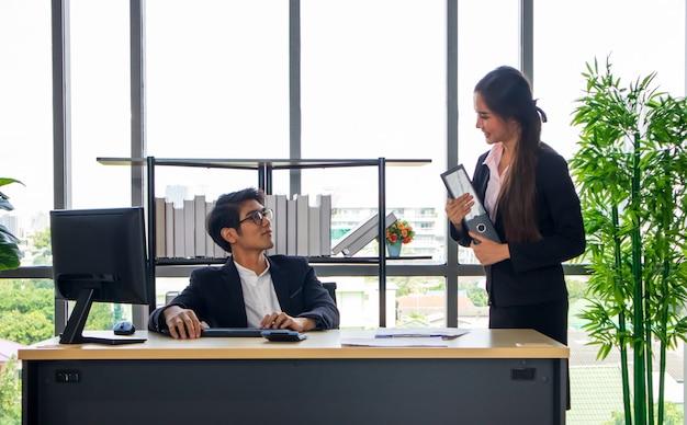 Un Jeune Homme D'affaires Asiatique Et Une Secrétaire Au Bureau Ensemble, Travaillez Jusqu'à La Fin Photo Premium