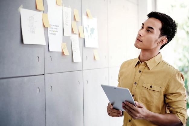 Jeune homme d'affaires asiatique travaillant sur une tablette numérique dans la salle de réunion de bureau. homme analysant des plans de données et un projet Photo Premium