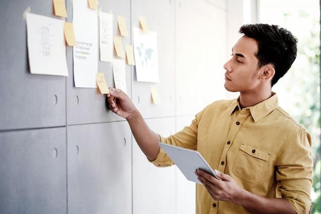 Jeune homme d'affaires asiatique travaillant sur une tablette numérique dans la salle de réunion de bureau Photo Premium