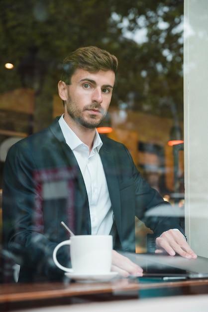 Jeune homme d'affaires assis dans le café avec ordinateur portable Photo gratuit