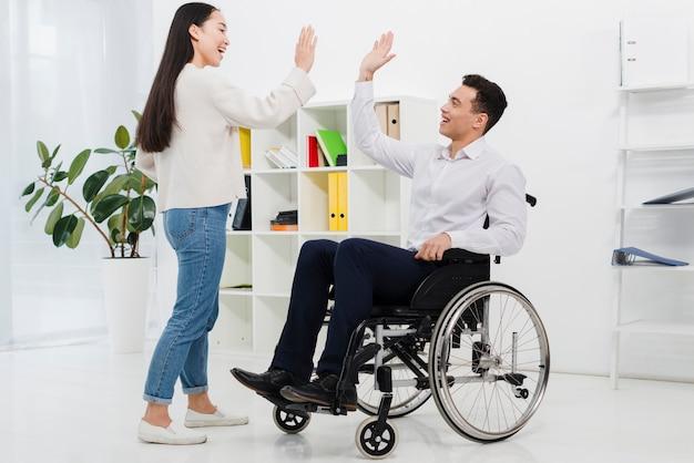 Jeune homme d'affaires assis sur un fauteuil roulant donnant un high-five à sa collègue au bureau Photo gratuit