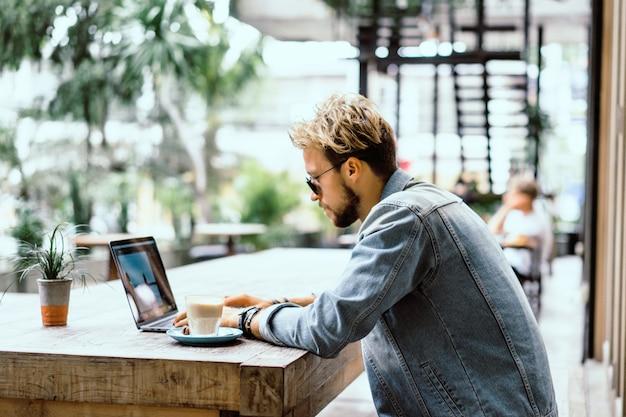 Jeune homme d'affaires attrayant dans un café travaille pour un ordinateur portable, boit du café. Photo gratuit