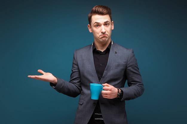 Jeune Homme D'affaires Attrayant En Veste Grise Et Chemise Noire Tenir Tasse Bleue Photo Premium