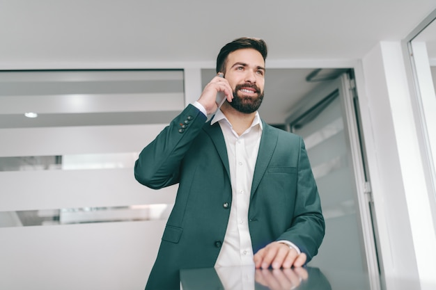 Jeune Homme D'affaires Barbu Caucasien Debout Dans Le Couloir Et Utilisant Un Téléphone Intelligent Pour Un Appel Professionnel. Photo Premium