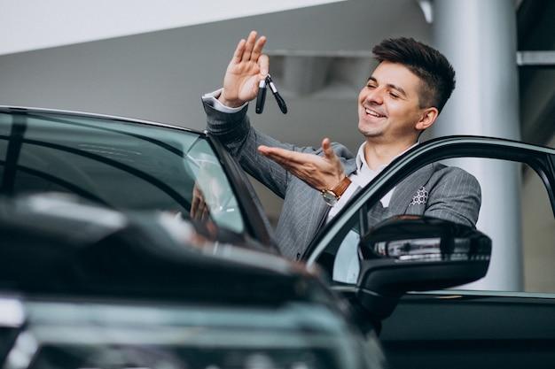 Jeune homme d'affaires beau choisir une voiture dans une salle d'exposition Photo gratuit