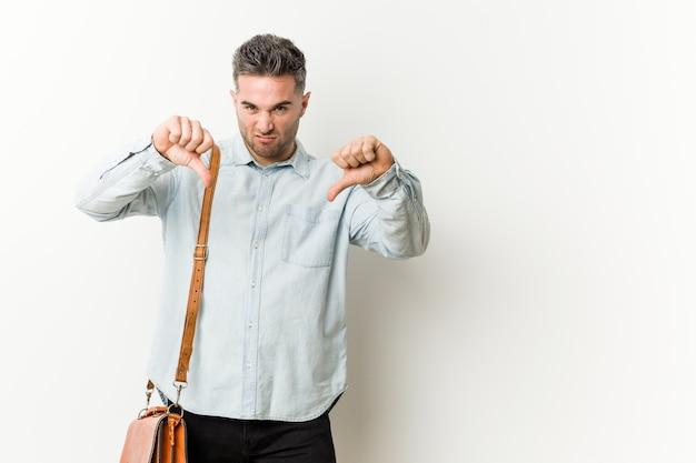 Jeune homme d'affaires beau montrant le pouce vers le bas et exprimant l'aversion. Photo Premium