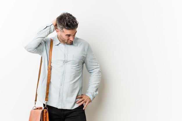 Jeune homme d'affaires beau toucher l'arrière de la tête, penser et faire un choix. Photo Premium
