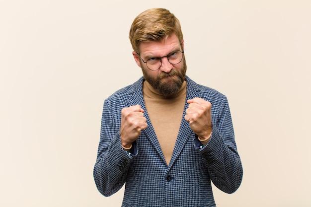 Jeune homme d'affaires blond à la recherche de confiance, en colère, fort et agressif, les poings prêts à se battre en position de boxe Photo Premium