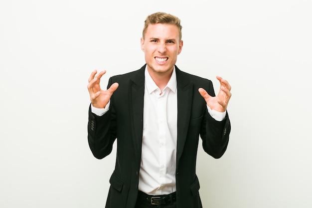Jeune Homme D'affaires Caucasien Bouleversé Crier Avec Les Mains Tendues. Photo Premium
