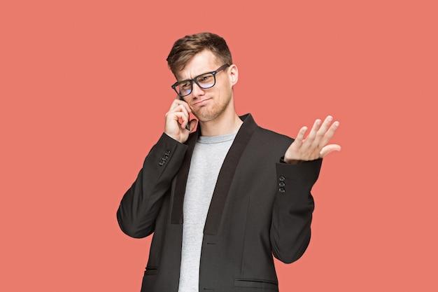 Le Jeune Homme D'affaires Caucasien Sur Fond Rouge, Parler Au Téléphone Cellulaire Photo gratuit