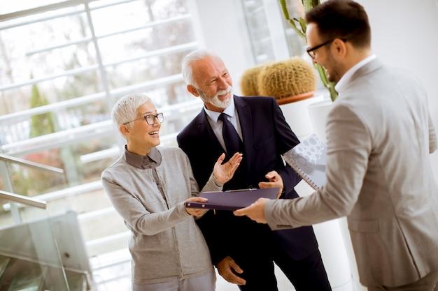 Jeune, homme affaires, à, clients aînés, permanent Photo Premium