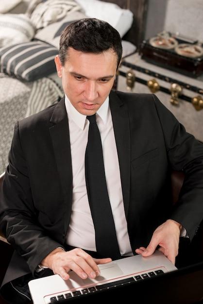 Jeune homme d'affaires confiant travaillant sur ordinateur portable Photo gratuit