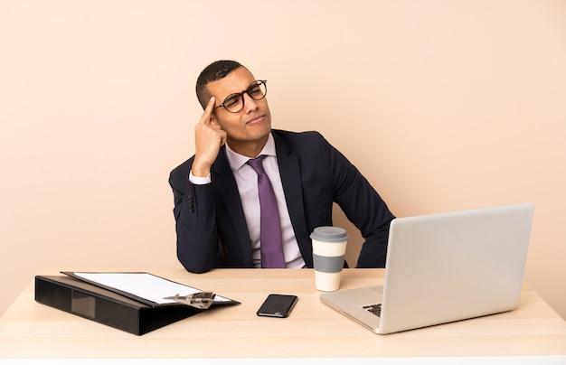 Jeune Homme D'affaires Dans Son Bureau Avec Un Ordinateur Portable Et D'autres Documents Ayant Des Doutes Et De La Pensée Photo Premium