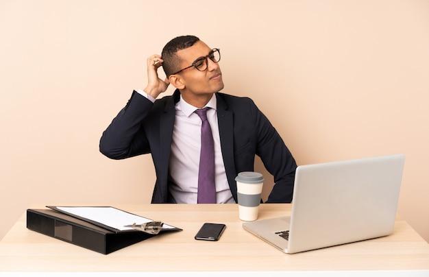 Jeune Homme D'affaires Dans Son Bureau Avec Un Ordinateur Portable Et D'autres Documents Ayant Des Doutes En Se Grattant La Tête Photo Premium