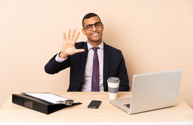 Jeune Homme D'affaires Dans Son Bureau Avec Un Ordinateur Portable Et D'autres Documents Comptant Cinq Avec Les Doigts Photo Premium