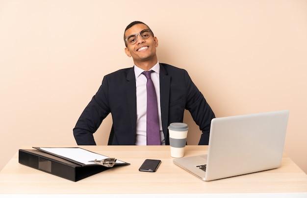 Jeune Homme D'affaires Dans Son Bureau Avec Un Ordinateur Portable Et D'autres Documents Posant Avec Les Bras à La Hanche Et Souriant Photo Premium