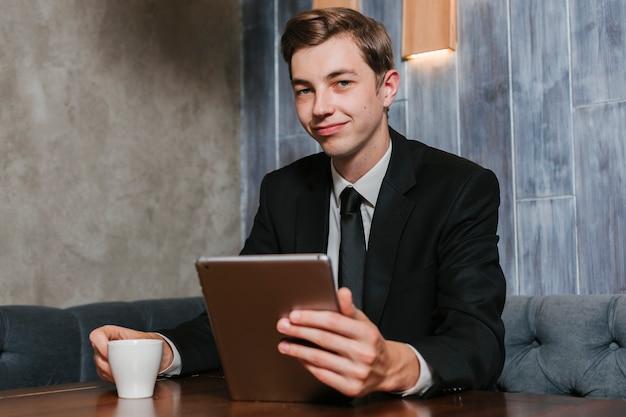Jeune homme d'affaires dans la tablette de bureau Photo gratuit