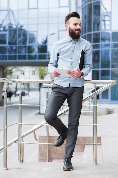 Jeune, homme affaires, debout, dehors, les, bâtiment entreprise, tenue, tablette numérique Photo gratuit