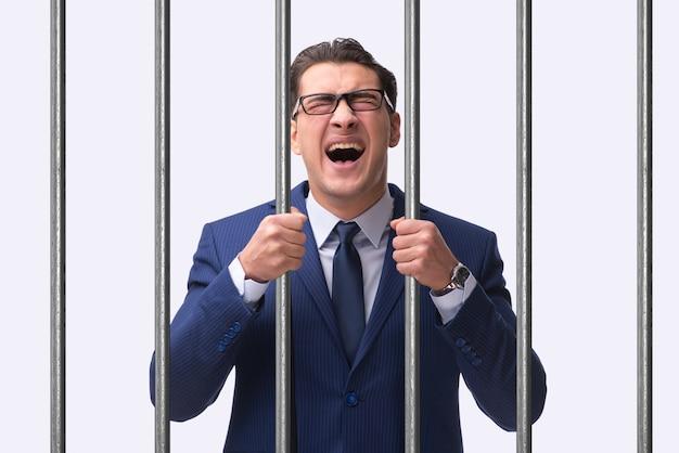 Jeune homme d'affaires derrière les barreaux en prison Photo Premium