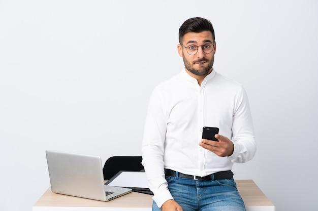Jeune Homme D'affaires Détenant Un Téléphone Mobile Ayant Des Doutes Et Avec Une Expression De Visage Confuse Photo Premium