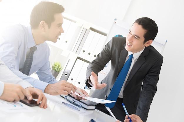 Jeune homme d'affaires discutant des travaux lors de la réunion Photo Premium