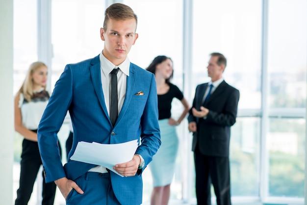 Jeune homme d'affaires avec des documents au bureau Photo gratuit