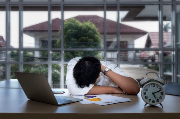Jeune homme d'affaires endormi et surmené près de l'ordinateur portable au bureau. Photo Premium