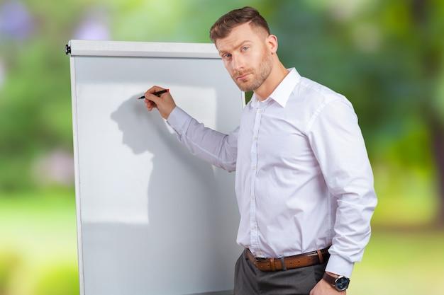 Jeune Homme D'affaires Ou Enseignant Montrant Sur Tableau Blanc Photo Premium